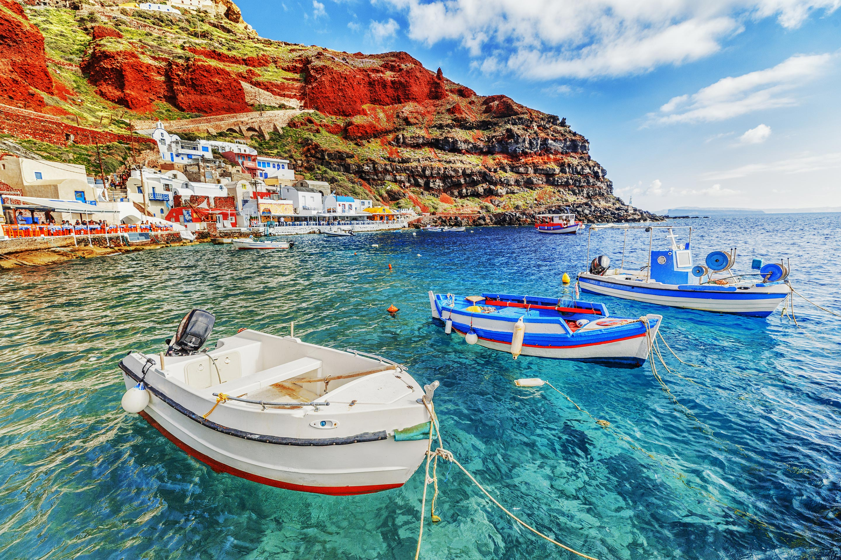 Fishing Boats In Crystal Clear Waters In Santorini, Greece